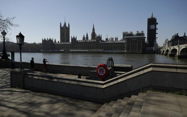 Vue d'ensemble des Chambres du parlement depuis la rive sud de la Tamise à Londres, le mercredi 25 mars 2020. (AP Photo/Matt Dunham)