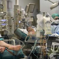 Sur cette photo prise derrière une vitre, des docteurs soignent des patients atteints du COVID-19 en soins intensifs à l'hôpital San Matteo à Padoue, dans le nord de l'Italie, le jeudi 26 mars 2020.  (Claudio Furlan/LaPresse via AP)