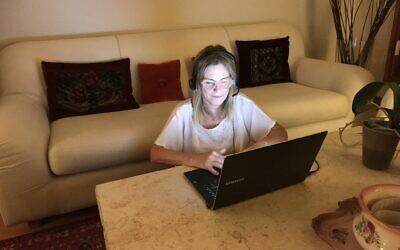 Odi Gruber, une volontaire d'ERAN, portant un casque dans sa maison de Toronto, où elle est volontaire pour prendre des appels d'Israël par son ordinateur. (Robert Sarner/ Times of Israël)