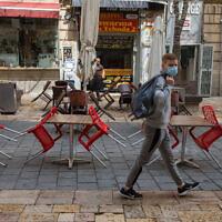 Un homme portant un masque passe à côté de restaurants fermés à Jérusalem, le 15 mars 2020. (Nati Shohat/Flash90)