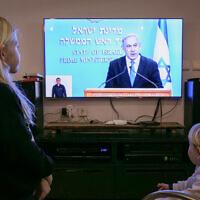 Des enfants israéliens regardent le Premier ministre Benjamin Netanyahu en train de faire une conférence de presse sur les nouvelles restrictions gouvernementales imposées au public concernant le COVID-19 le 19 mars 2020. (Photo par Chen Leopold/Flash90)