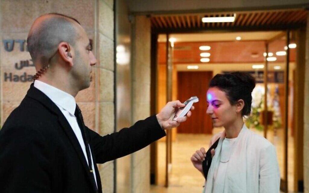 Un employé de la Knesset contrôle la température d'une femme entrant au parlement, le 16 mars 2020. (Knesset / Adina Velman)
