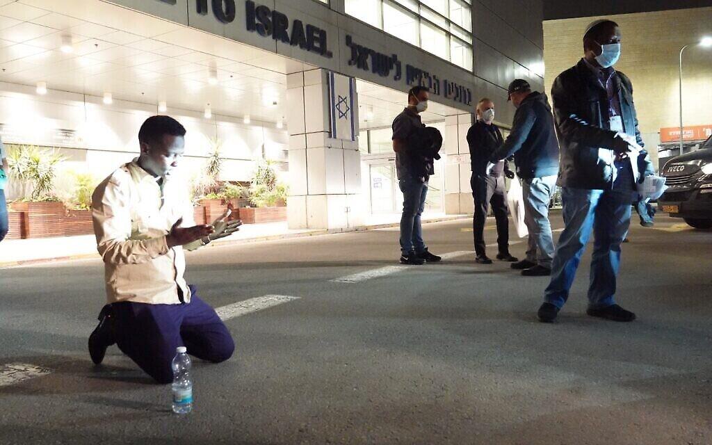 Un immigrant éthiopien s'agenouille peu après son arrivée à l'aéroport Ben Gurion, le 24 mars 2020. (Michael Dimenstein/ GPO)
