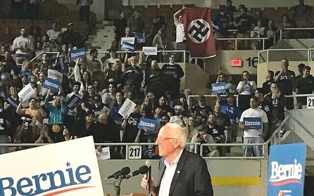 Un homme déroule un drapeau nazi lors d'un meeting de Bernie Sanders dans l'Arizona le 5 mars 2020. (Capture écran/YouTube)
