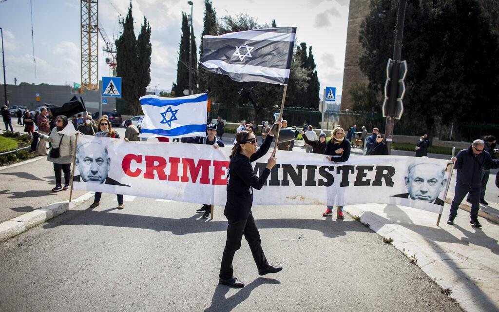 Des citoyens agitent des drapeaux israéliens, lors d'une manifestation devant le Parlement israélien à Jérusalem, le jeudi 19 mars 2020, accusant le gouvernement du Premier ministre Benjamin Netanyahu d'exploiter la crise du coronavirus pour consolider son pouvoir et saper les fondements démocratiques d'Israël. (Crédit : AP / Eyal Warshavsky)