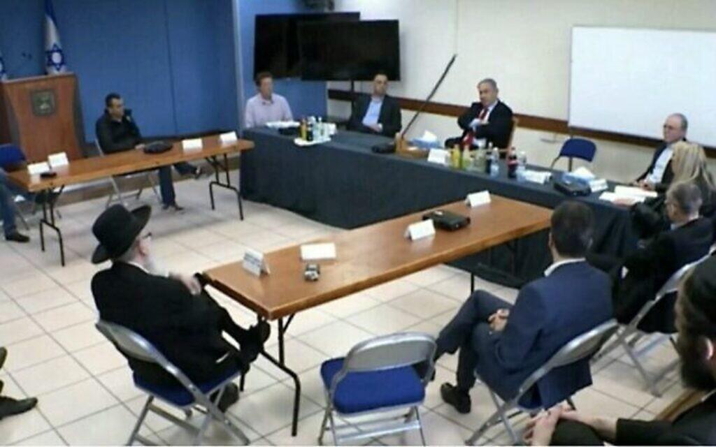 Le Premier ministre Benjamin Netanyahu tient une réunion pour décider des mesures à prendre pour contenir le coranavirus. Les participants sont assis à distance les uns des autres, le 13 mars 2020. Le Prof. Avi Simhon est le deuxième en partant de la droite. (Capture d'écran/Douzième chaîne)