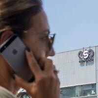Une femme israélienne utilise son téléphone devant un bâtiment à Herzliya qui héberge la société de renseignement du groupe NSO, le 28 août 2016. (Jack Guez/AFP/Fichier)