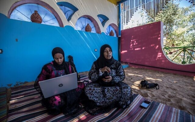 """Hafsa Amberkab (R) and Fatma Addar (L), Nubian Egyptian women who compiled a handy dictionary of some 230 words in the Kenzi dialect, speak to an AFP journalist as they show off a Nubian lexical chart in the village of Gharb Suhail, near Aswan in Upper Egypt, some 920 kilometres south of the capital Cairo, on February 3, 2020. - Addar grew up in a Nubian family but as a child was schooled mostly in Arabic -- only hearing her ancestral tongue when spoken by the family elders. Amberkab, an entrepreneur, launched the initiative """"Koma Waidi"""" -- meaning tales from the past -- documenting stories told by elders and collecting dying expressions. According to locals, the Nubian language is unpractised by many after their mass eviction from their ancestral lands to make way for the construction of the Aswan High Dam on the Nile in the 1960s. (Photo by Khaled DESOUKI / AFP)"""