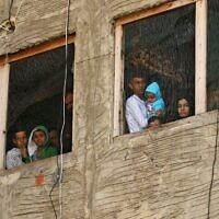 Des réfugiés syriens observent depuis les fenêtres d'un bâtiment en construction qu'ils utilisent comme abri dans la ville de Sidon du sud du Liban, le 17 mars 2020. (Photo par Mahmoud ZAYYAT / AFP)