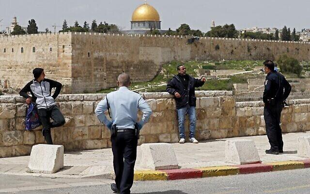 Des policiers israéliens ordonnent à des gens, aux abords de la Vieille Ville de Jérusalem, de rentrer chez eux dans le cadre des directives de lutte contre le coronavirus, le 27 mars 2020 (Crédit : Ahmad Gharabli/AFP)