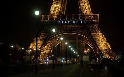 Illustration. La tour Eiffel, à Paris, le 27 mars 2020, avec le message «Stay at Home» («Restez chez vous») dans le cadre de la lutte contre l'épidémie de coronavirus. (Crédit : Thomas SAMSON / AFP)