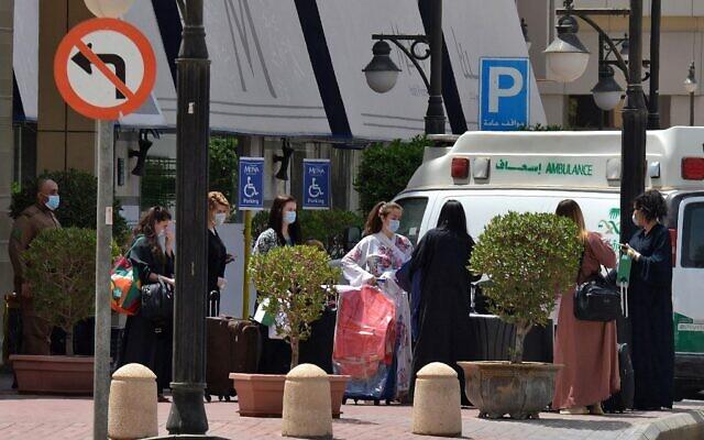 Des touristes portant des masques quittent l'hôtel Mena à Ryad le 30 mars 2020 après y avoir séjourné en quarantaine. (Photo par FAYEZ NURELDINE / AFP)