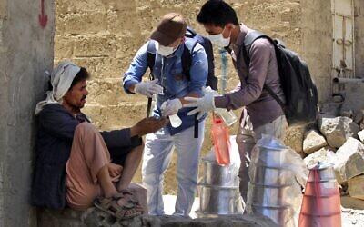 Des volontaires yéménites désinfectent les mains d'un homme dans l'un des quartiers pauvres de Sanaa, le 30 mars 2020, en pleine épidémie de COVID-19. (Crédit : MOHAMMED HUWAIS / AFP)
