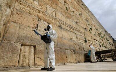 Des employés municipaux désinfectent le mur Occidental, le lieu le plus saint où les Juifs peuvent prier, le 31 mars 2020 en pleine épidémie du COVID-19 à Jérusalem. (Photo par Emmanuel DUNAND / AFP)
