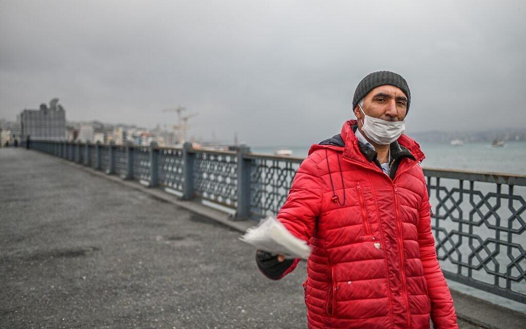 Un vendeur tente de vendre des masques de protection sur le pont vide de Galata le 1 avril 2020 à Istanbul, après que des responsables turcs ont appelé les citoyens à rester à la maison et à respecter les règles de distanciation sociale. (Crédit : Ozan KOSE / AFP)