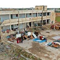 Cette photo du 1 avril 2020 montre un bâtiment d'école fortement endommagé par d'anciens bombardements. Il est actuellement habité par des familles déplacées dans la ville de Binnish tenue par les rebelles dans la province d'Idleb du nord est de la Syrie. (Photo par Omar HAJ KADOUR / AFP)