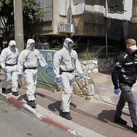 Des policiers israéliens, en tenue de protection, arrivent dans une yeshiva dans la ville israélienne de Bnei Brak le 2 avril 2020, pour s'assurer que les mesures de distanciation sociale imposées par les autorités israéliennes visant à freiner la propagation du nouveau coronavirus sont respectées. (Crédit : JACK GUEZ / AFP)