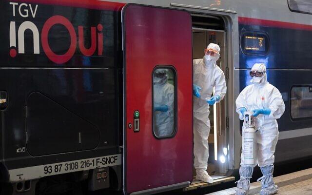 Le personnel médical attend qu'un patient infecté par le COVID-19 soit embarqué à bord d'un train à grande vitesse TGV médicalisé à la gare de Strasbourg, dans l'est de la France, le 3 avril 2020, lors de l'évacuation de 24 patients vers des hôpitaux de Bordeaux dans le sud-ouest de la France. (Crédit : PATRICK HERTZOG / POOL / AFP)