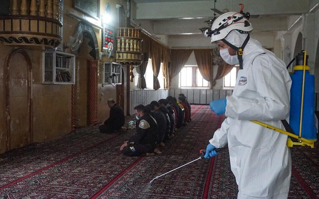 Des membres de la Défense civile syrienne, surnommés Casques blancs, font la prière du vendredi alors qu'un autre désinfecte la mosquée déserte dans la ville tenue par les rebelles de Binnish dans la province d'Idlib au nord-ouest de la Syrie, le 3 avril 2020 pendant l'épidémie de COVID-19. (Photo par Muhammad HAJ KADOUR / AFP)