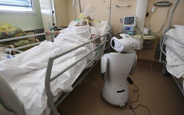 L'un des six robots de l'hôpital Circolo di Varese se tient près d'un patient, le 3 avril 2020, afin d'aider le personnel de santé du département de médecine de haute intensité à soigner douze patients souffrant de l'épidémie de coronavirus. (Crédit : Miguel MEDINA / AFP)