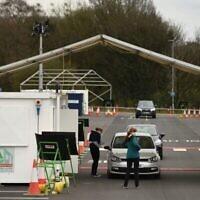 Des employés du NHS se font dépister pour le Covid-19 dans un site de test mis en place sur un parking de la périphérie de Manchester, le 4 avril 2020. (Oli SCARFF / AFP)