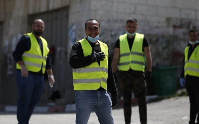 Des bénévoles palestiniens s'occupent d'un barrage pour mesurer la température des habitants à l'entrée du village d'Ein Yabrud, situé à proximité de Ramallah. Des civils ont été déployés le long de routes rurales de la Cisjordanie pour réaliser des contrôles en pleine épidémie de COVID-19, le 6 avril 2020.  (Photo par ABBAS MOMANI / AFP)