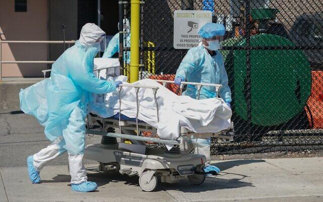 Des corps sont acheminés dans un camion frigorifique servant de morgue temporaire à l'hôpital Wyckoff dans le quartier de Brooklyn, le 6 avril 2020 à New York. (Bryan R. Smith / AFP)