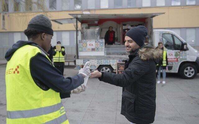 Un bénévole propose du désinfectant pour les mains lors d'une campagne d'information en plusieurs langues sur la nouvelle pandémie de coronavirus COVID-19, dans la banlieue de Tensta à Stockholm, qui abrite un grand nombre d'immigrants, le 12 avril 2020. (Crédit : ALI LORESTANI / TT Agence de presse / AFP) / Suède OUT)