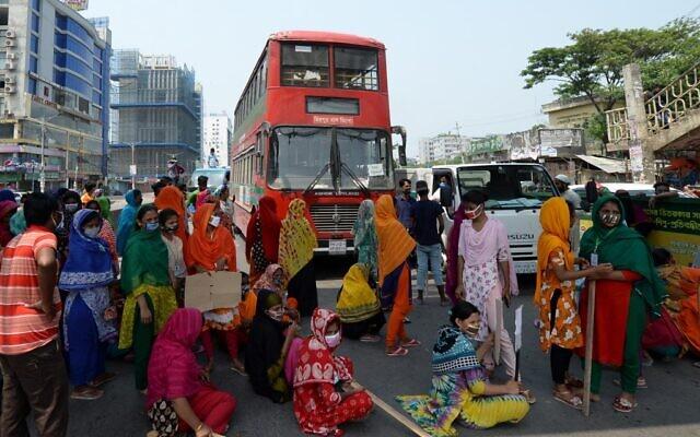 Des travailleurs du secteur du vêtement bloquent une route lors d'une manifestation pour exiger le paiement de leur salaire, à Dacca le 13 avril 2020. (Crédit : MUNIR UZ ZAMAN / AFP)