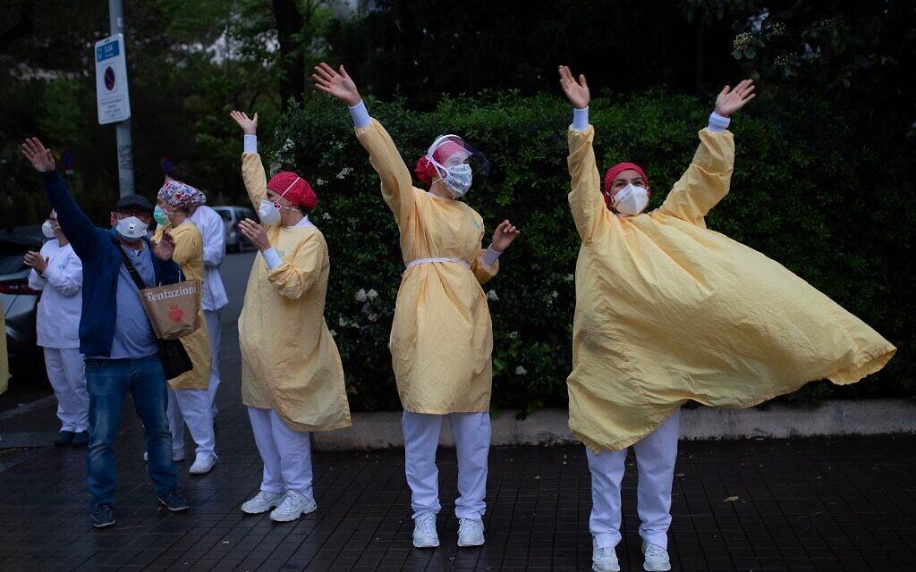 Des personnels médicaux portant des masques et des combinaisons de protection lors des applaudissements à l'extérieur de l'hôpital de Barcelone, le 13 avril 2020. (Crédit : Josep LAGO / AFP)