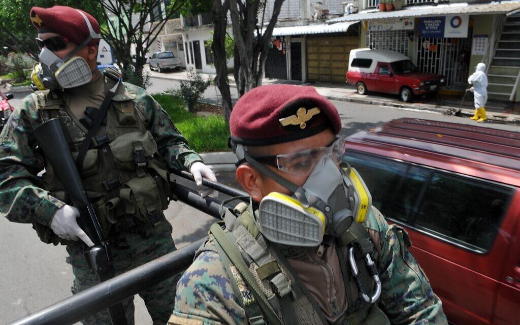 Des soldats patrouillent dans les rues du quartier Cisne 2, le long des rives de la rivière Estero Salado, à Guayaquil, en Équateur, le 14 avril 2020 dans le cadre de la pandémie de coronavirus. (Crédit : Jose SANCHEZ / AFP)
