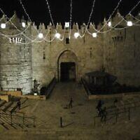 Des gens déambulent sous les lumières qui décorent la porte de Damas dans la Vieille Ville de Jérusalem, alors que les musulmans du monde entier se préparent à fêter le Ramadan dans un contexte de pandémie de coronavirus, le 19 avril 2020 (Crédit : Ahmad Gharabli/AFP)