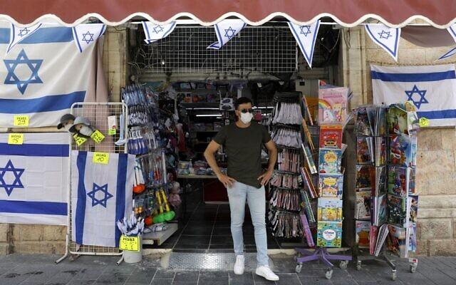Le propriétaire d'un magasin devant son échoppe, après l'allègement du confinement, à Jérusalem, le 21 avril 2020. (Crédit : MENAHEM KAHANA / AFP)