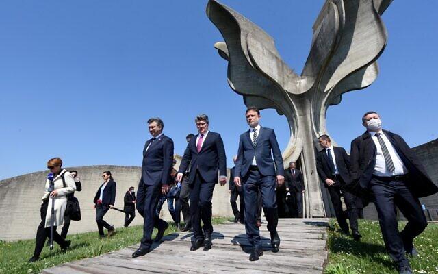 Le président du Parlement croate Gordan Jandrokovic (à droite), le président croate Zoran Milanovic (au centre) et le Premier ministre croate Andrej Plenkafterovic (à gauche) quittent le monument en forme de fleur après une cérémonie en hommage aux dizaines de milliers de victimes tuées dans le camp de concentration de Jasenovac durant la Seconde Guerre mondiale, le 22 avril 2020. (Crédit : Denis LOVROVIC / AFP)
