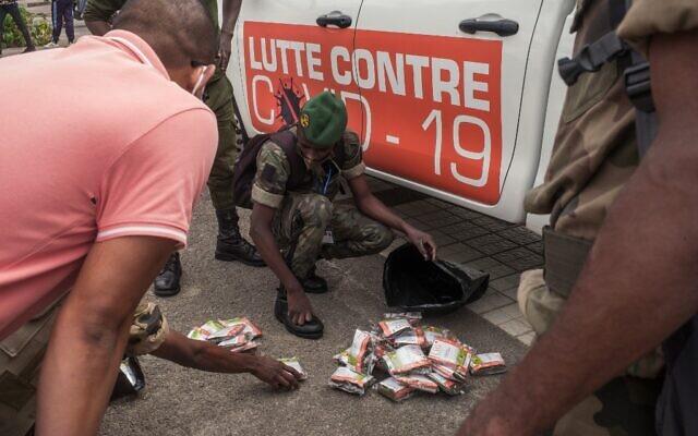 Les soldats de l'armée malgache sur la place devant l'hôtel de ville d'Antananarivo, le 22 avril 2020, pour recevoir des stocks d'une tisane locale, présentée par le président Andry Rajoelina comme un puissant remède contre le coronavirus COVID-19, à distribuer aux habitants. Baptisée Covid-Organics, la tisane est dérivée de l'armoise, une plante dont l'efficacité dans le traitement du paludisme a été prouvée, et d'autres herbes indigènes. (Crédit : RIJASOLO / AFP)