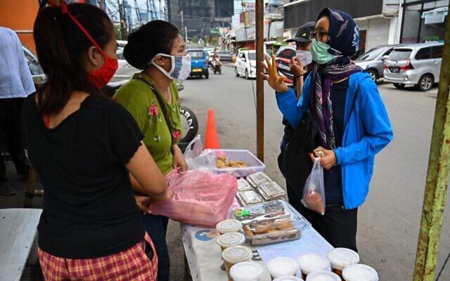 Des Indonésiens achètent de la nourriture pour la rupture du jeûne lors du premier jour du Ramadan à Jakarta, le 24 avril 2020, en pleine pandémie de coronavirus. (BAY ISMOYO / AFP)