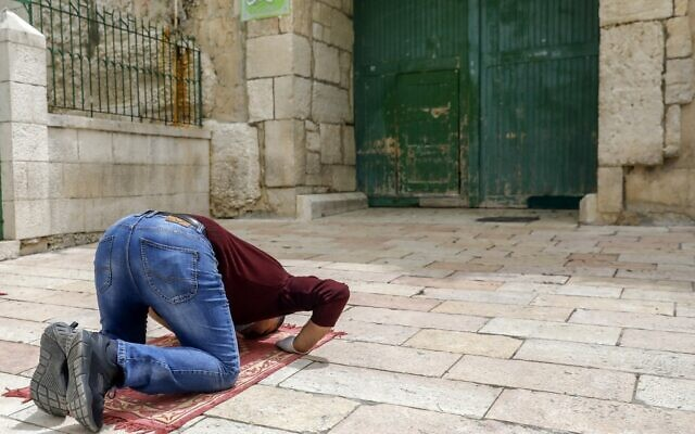 Un fidèle palestinien effectue la première prière du vendredi du mois de jeûne sacré du Ramadan, à l'extérieur de l'enceinte de la mosquée fermée d'al Aqsa dans la vieille ville de Jérusalem, le 24 avril 2020, au milieu de mesures de sécurité et de distanciation sociale accrues en raison de la pandémie de coronavirus. (AHMAD GHARABLI / AFP)