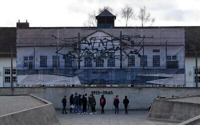 Des visiteurs se tiennent devant le Mémorial international de l'ancien camp de concentration de Dachau, dans le sud de l'Allemagne, le 09 décembre 2019. - L'ancien camp de Dachau, construit en 1933 et qui a servi de modèle à tous les autres camps de concentration en Europe, a été mis à profit par le gouvernement de Bavière, la région dans laquelle il est situé. (Crédit : Christof STACHE / AFP)