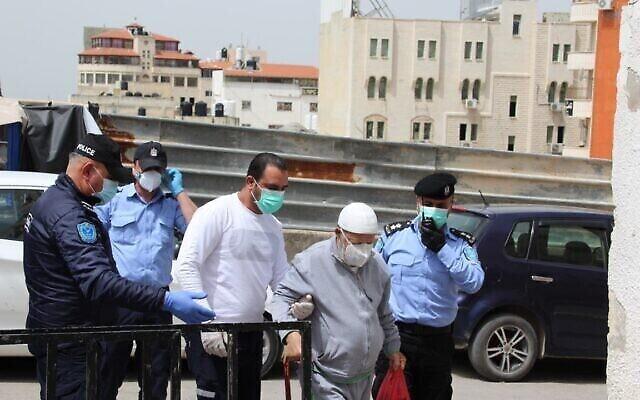 Les forces de sécurité de l'AP et un homme âgé près de l'entrée de l'hôpital Thabet Thabet de Tulkarem, en Cisjordanie, le 5 avril 2019 (Crédit : : Wafa)