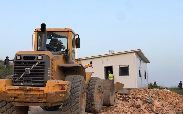 Des agents de l'administration civile se préparent à démolir une maison dans l'avant-poste de Kumi Ori, le 22 avril 2020. (Autorisation)