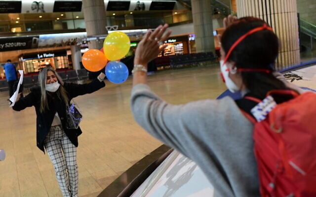 Des passagers israéliens accueillis avec joie à l'aéroport Ben Gurion, le 23 mars 2020 (Crédit : Tomer Neuberg/Flash90)