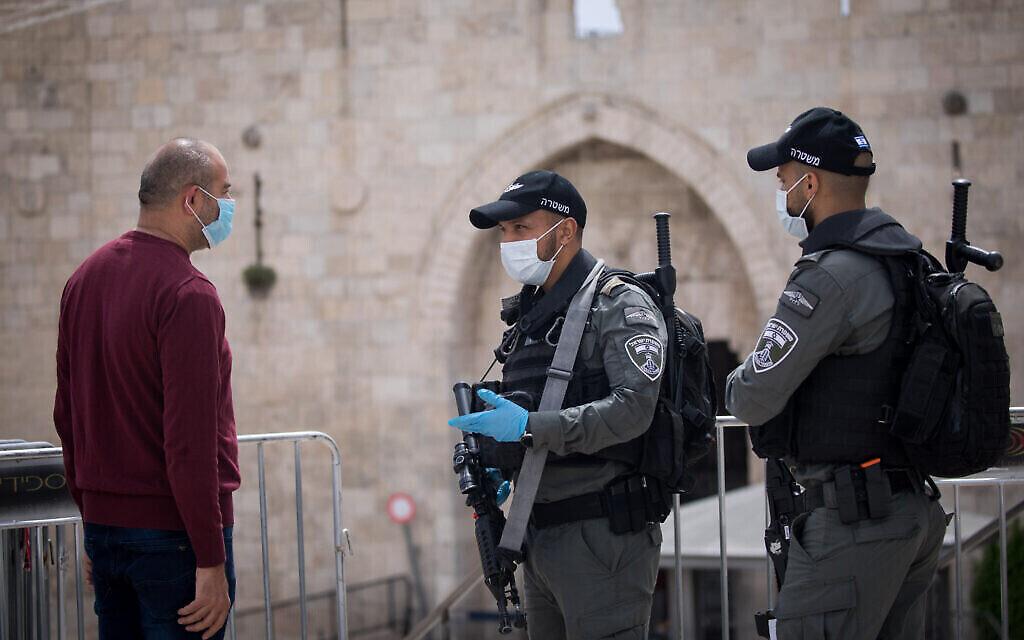 Des agents de la police des frontières israéliennes parlent avec un homme à la porte de Damas dans la Vieille Ville de Jérusalem lors du 1er jour du Ramadan, le 24 avril 2020 (Crédit : Yonatan Sindel/Flash90/ via JTA)