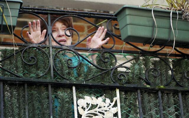 Sur cette photo du 19 mars 2020, Alice Rosenberg, survivante de la Shoah, parle à Freida Rothman, une bénévole qui livre des repas, depuis son balcon à Brooklyn, New York. (AP Photo/Jessie Wardarski)