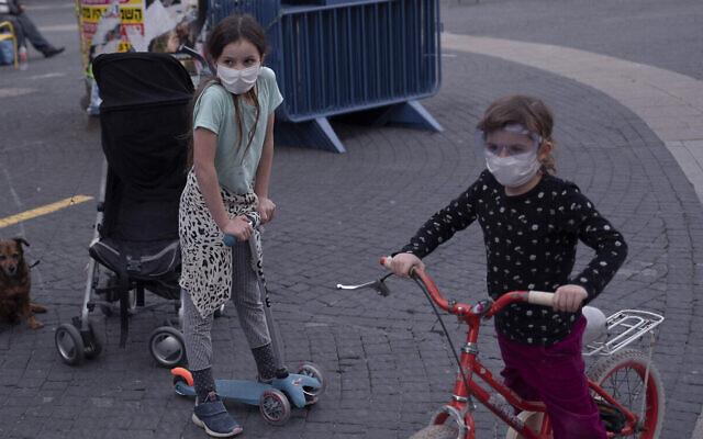 Des enfants portent des masques en pleine pandémie de coronavirus, à Tel Aviv, le 24 mars 2020. (Crédit : AP Photo/Oded Balilty)