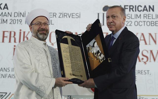 Le président turc Recep Tayyip Erdogan, à droite, reçoit un cadeau de la part du chef des Affaires religieuses de Turquie Ali Erbas lors d'un Sommet religieux africain musulman à Istanbul, le samedi 19 octobre 2019. (Service de presse présidentiel via AP, Pool )