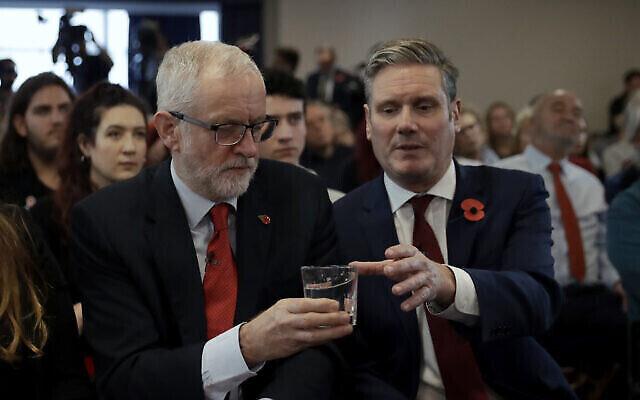 Le leader du parti du Labour britannique, Jeremy Corbyn, à gauche, donne un verre d'eau au secrétaire d'Etat au Brexit du cabinet fantôme, Keir Starmer, lors d'un événement de campagne sur le Brexit à Harlow, en Angleterre, le 5 novembre 2019 (Crédit : AP Photo/Matt Dunham)