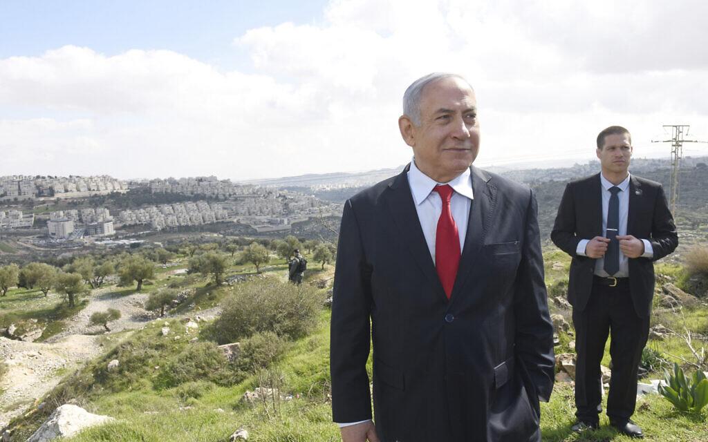 Le Premier ministre Benjamin Netanyahu se trouve devant une vue d'ensemble du quartier de Har Homa à Jérusalem-Est, où il a annoncé la construction d'un nouveau quartier, le 20 février 2020. (Debbie Hill/Pool via AP)