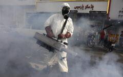 Un pompier désinfecte une place pour lutter contre le nouveau coronavirus, dans l'ouest de Téhéran, en Iran, le 13 mars 2020. (Vahid Salemi/AP)