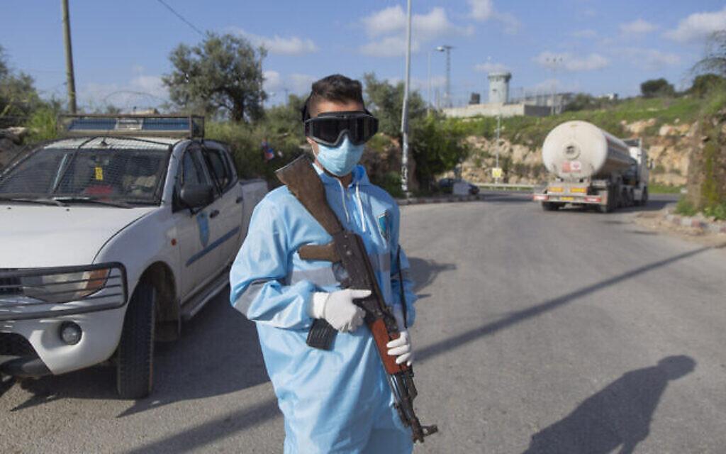 Un policier palestinien à un poste de contrôle pour réceptionner et enregistrer les travailleurs sortant d'un poste de contrôle de l'armée israélienne, sur le chemin du retour à la fin d'une journée de travail en Israël, près du village de Nilin en Cisjordanie, à l'ouest de Ramallah, le mercredi 25 mars 2020. (AP/Nasser Nasser)