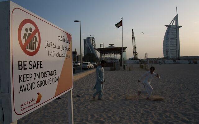 Sur cette photo du vendredi 20 mars 2020, deux employés s'amusent à côté d'un panneau rappelant à la population de garder ses distances les uns des autres afin de limiter la propagation du COVID-19 devant l'hôtel de luxe Burj Al Arab à Dubai, Emirats arabes unis. (AP Photo/Jon Gambrell, File)